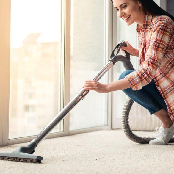 Lady vacuuming carpet | McSwain Carpet & Floors