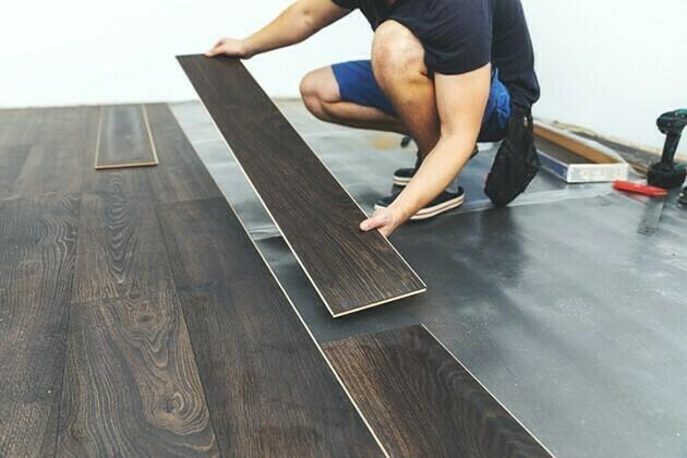 laminate flooring - worker installing new floor | McSwain Carpet & Floors
