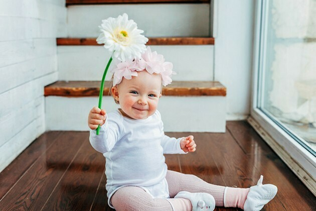 Little baby girl wearing spring wreath siting on floor in bright light living room near window and playing with gerbera flowers | McSwain Carpet & Floors