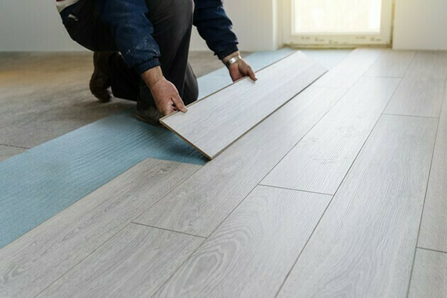 Worker carpenter doing laminate floor work | McSwain Carpet & Floors